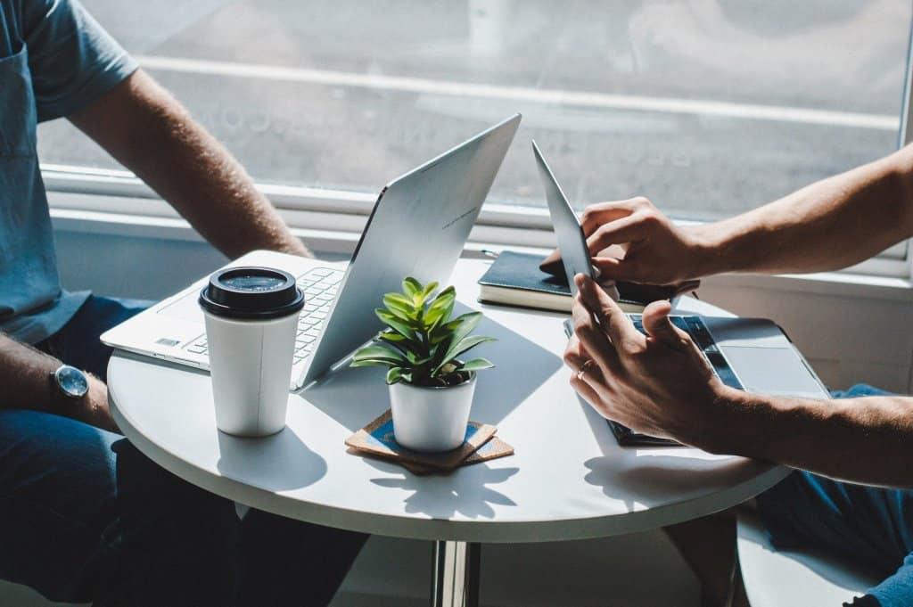 Laptop Tablet Tisch Konversation Verhandlung Kaktus Kaffee Becher Kundengespräch